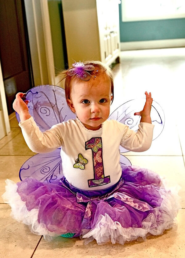 Little girl with purple ruffle skirt, number 1 on her shirt, and purple butterfly wings for her first enchanted butterfly party