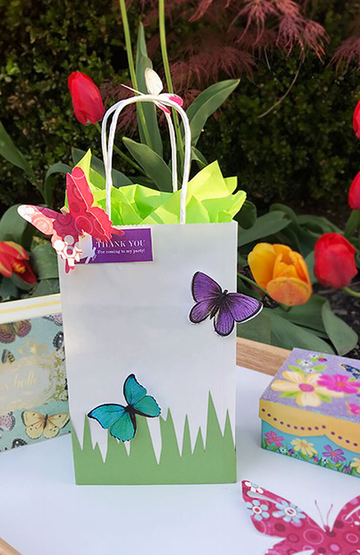 White gift bag or party favor with green paper grass and colorful butterflies for Enchanted Butterfly Party Ideas