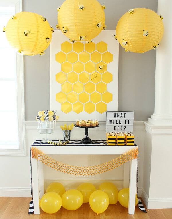 What will it BEE? Gender Reveal party display with yellow lanterns, balloons, and hexagon backdrop.