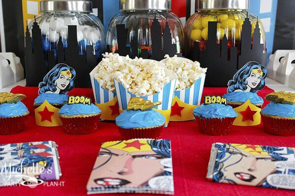 Love the city skyline silhouette wrapping the candy jars and the custom made comic page snack bags. Wonder Woman Party Food | Halfpint Design, party ideas, party themes