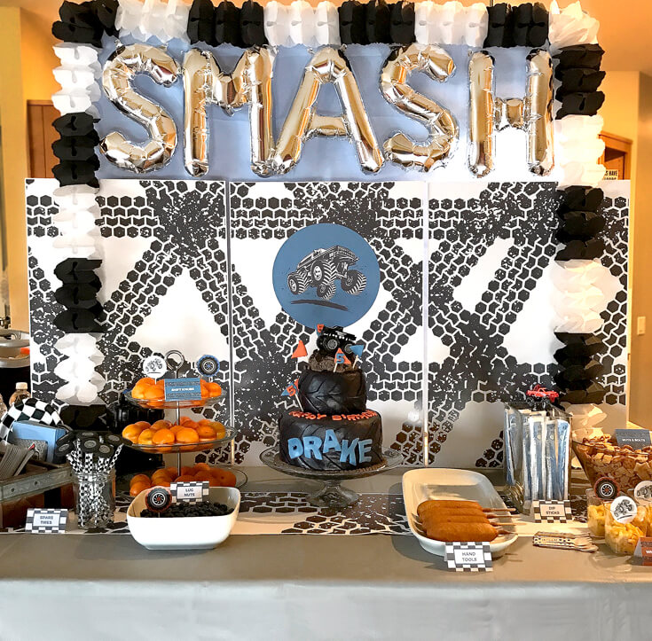 Great backdrop for a fun party. Easy to do with large photos, a table cover, letter balloons, and a tissue paper garland. Monster Truck Birthday Party Smash! Halfpint Design with Party Printables from HalfpintPartyDesign on Etsy. Boy party theme. 5th birthday. Boy theme.