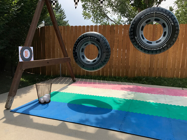 "The ""Hole Shot"" activity was a tough one for the 5 year old crowd. Toss a ball through the open hole of huge inflatable tires. For older kids have the tires spin slowly for an added challenge. Monster truck activity ideas-halfpintpartydesign.com-boy party theme"