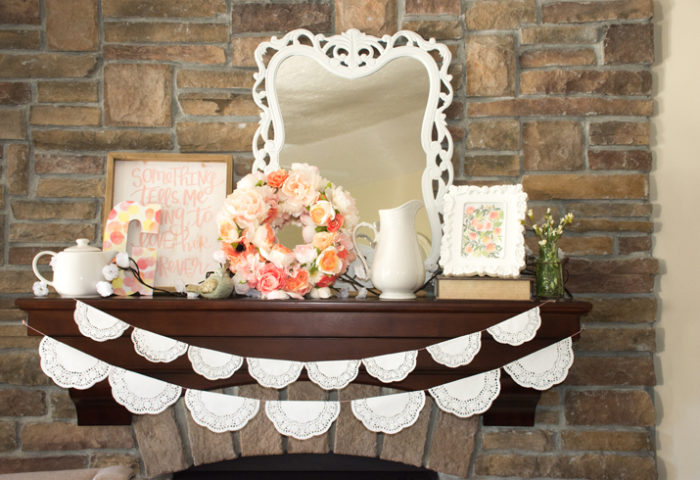 "Choose your focal points. This mantel is a prominent feature and styling it with additional nursery decor was a great idea. A ""G"" for Georgia, another piece of sweet nursery art ""Something tells me I'm going to love her forever"", a mirror, and a lovely floral wreath made my mommy-to-be. The doilie garlands are so cute and very easy to make. - Sweet Little Peach Baby Shower 