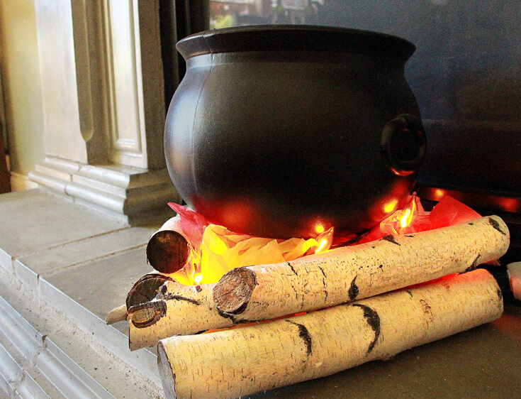 Step 5: Balance the cauldron so it is slightly inside the triangle. Create an Eerie Witches' Cauldron | Halfpint Design - Halloween decorations, witch decor, faux fire, fake campfire, firelight bulbs