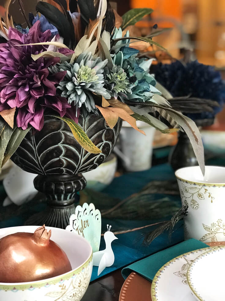 Fun turquoise florals with peacock feathers, copper accents, and peacock place cards make for fabulous Thanksgiving, Christmas, or dinner party centerpieces. See more Global Chic Holiday Tablescape ideas at Halfpint Design. Thanksgiving Tablescape, Place setting, Christmas Table, Holiday decor.