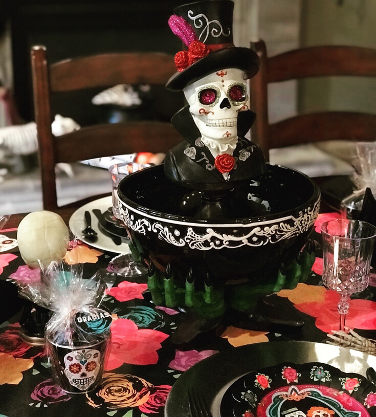 Simple Day of the Dead Coco Movie Party centerpiece created by adding a Sugar skull bust to a Halloween serving bowl. Get creative and shop your house! You'll be surprised how much you can use. Coco Viewing Party Tips at Halfpint Design. Day of the Dead Party, Dia de los Muertos, Coco birthday party