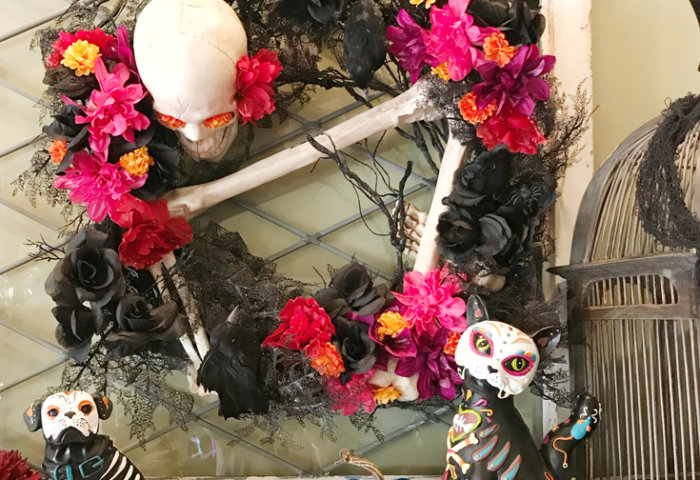 The finished Day of the Dead Wreath! I love all the colors and how bright and cheery it has now become. The skeleton is made even less menacing with the sugar skull cat and dog figures on the mantel. Day of the Dead Wreath Transformation from Halfpint Design. Day of the Dead party, Dia de los Muertos decor, Decor DIY
