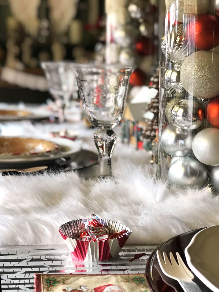 Looking for some good ol' fashioned Christmas decor? Fill large hurricane vases with ornaments for a simple yet stunning centerpiece. Check out all the details of this Cozy Cottage Christmas Tablescape on Halfpint Design. Farmhouse Style Christmas table, Vintage Christmas.