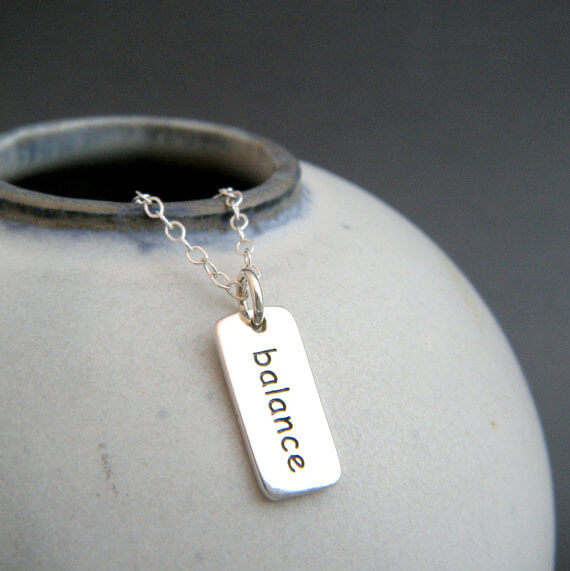 "Silver necklace hand stamped with ""balance"" on silver chain draped over pot"