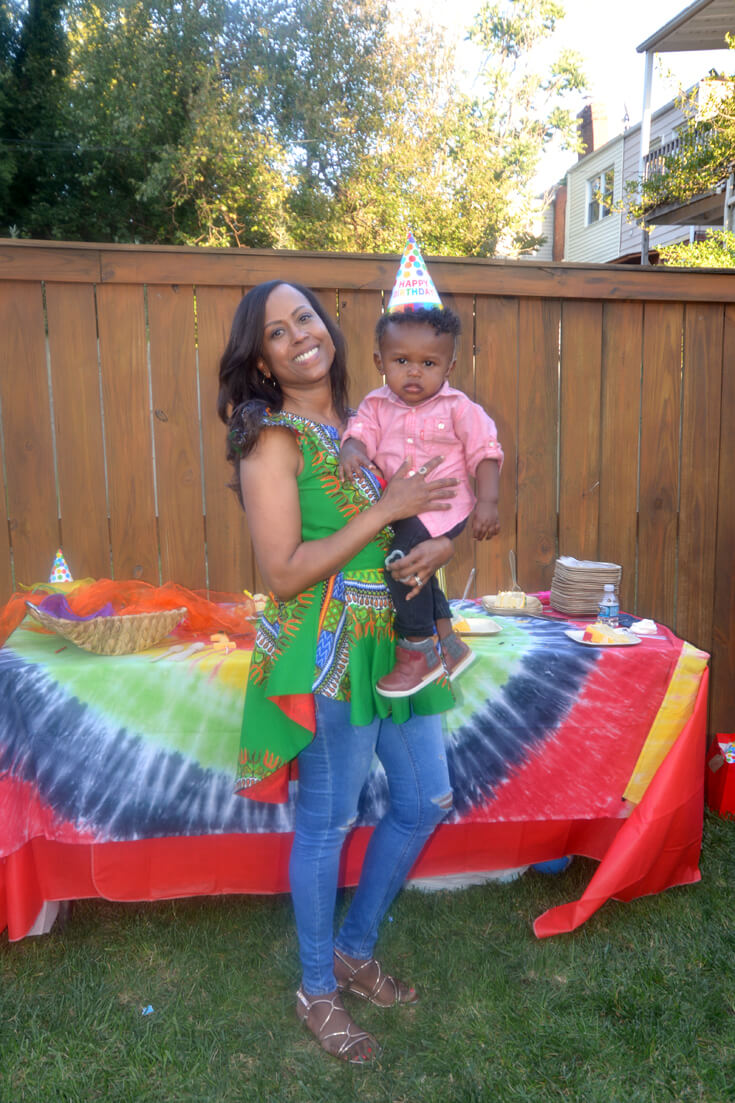Woman holding baby with party hat on. Tie dyed tablecloth behind them for ONE LOVE first birthday party