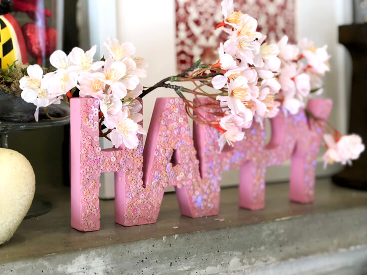 Pink sequin letters spell HAPPY with a cherry blossom spray. Romantic Valentine's Day Mantel Decor on Halfpint Design.