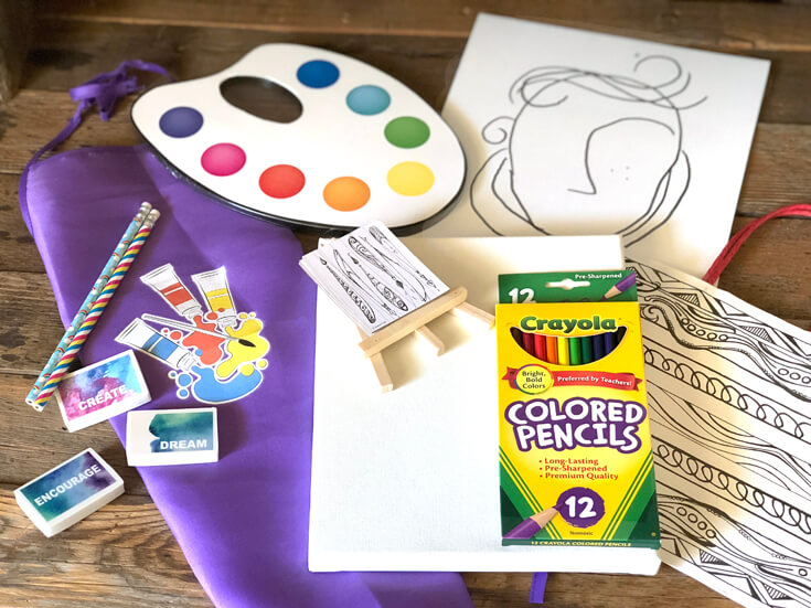 Art supplies laid out on wooden background as party favors for an Art Party