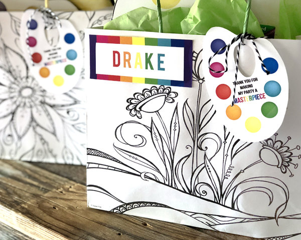 Black and white floral bag with rainbow name tag and a personalized paint palette tag as an Art Party Favor