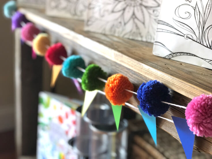 Colorful pom pom garland and pennant banner on wooden hutch for an Art Party