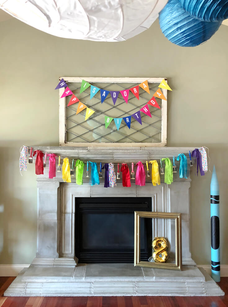 Mantel decorated with rainbow colored banners for an Art themed birthday party and paint brush garland