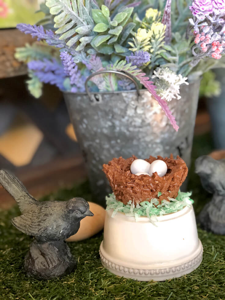 "Chocolate bird nest Easter treat on bed of coconut ""grass"" with metal bird and galvanized bucket full of faux spring flowers."