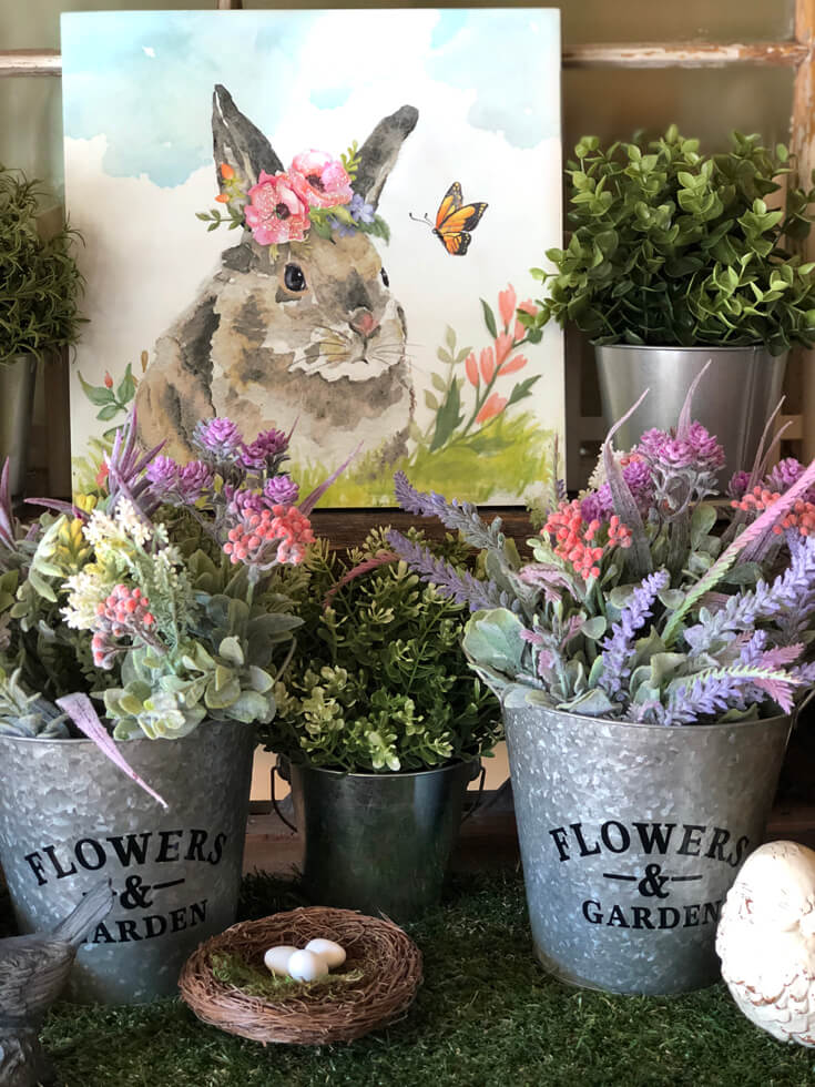 Easter decor on grass mat, galvanized buckets with flowers, and Bunny art.
