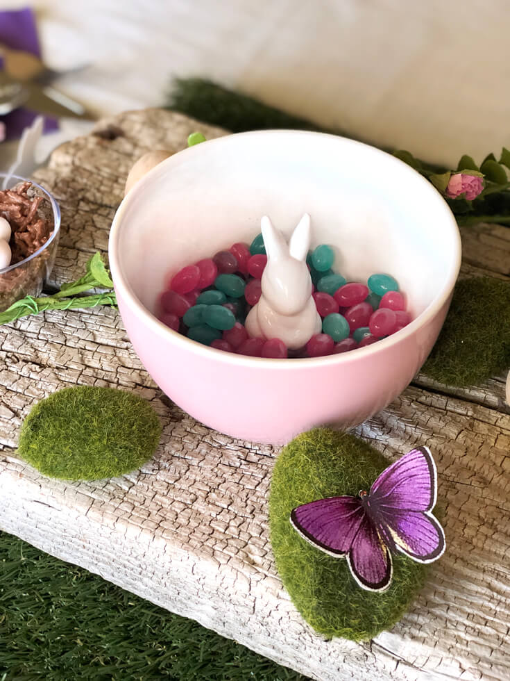 Ceramic bowl with little bunny instead surrounded by jelly beans. Moss and butterfly on wooden board. Easter tablescape.