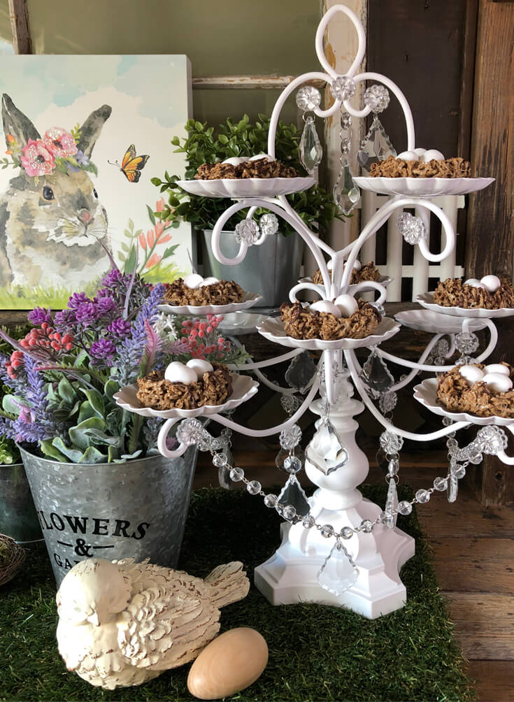 Marshmallow cereal bird nests with Cadbury mini-eggs on white tiered cupcake stand