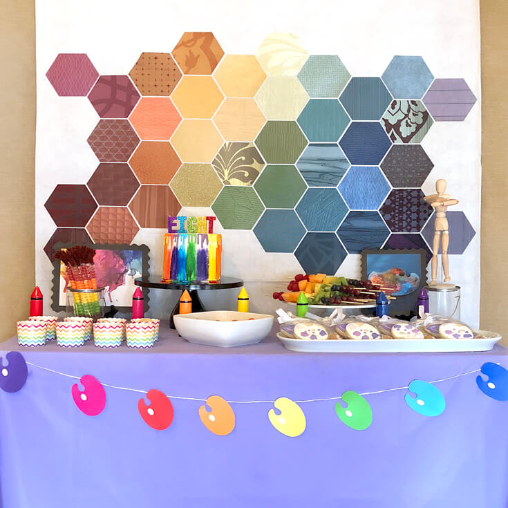 Rainbow colored hexagons arranged to create a backdrop for a colorful art party food table