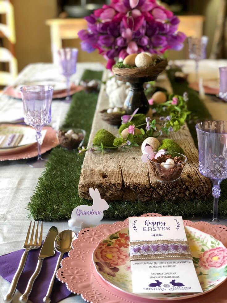 Fully decoration table for Easter dinner. Grass runner with rustic wood board, moss, bunnies, butterflies, and tulips.