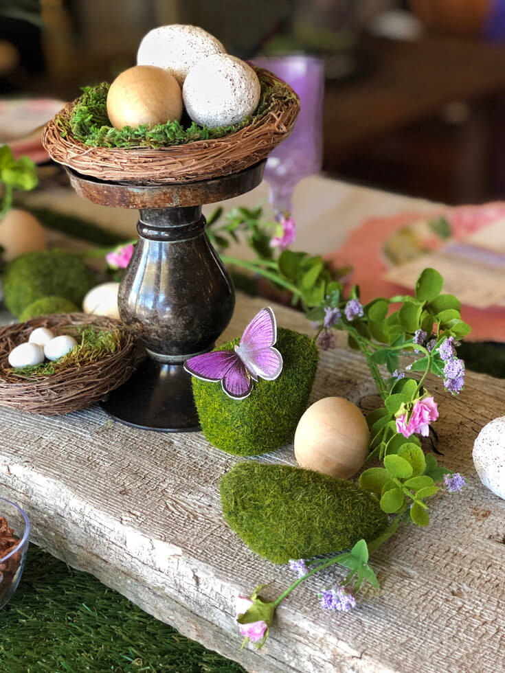 moss butterflies and bird nests with mini eggs on wooden board as an Easter table centerpiece