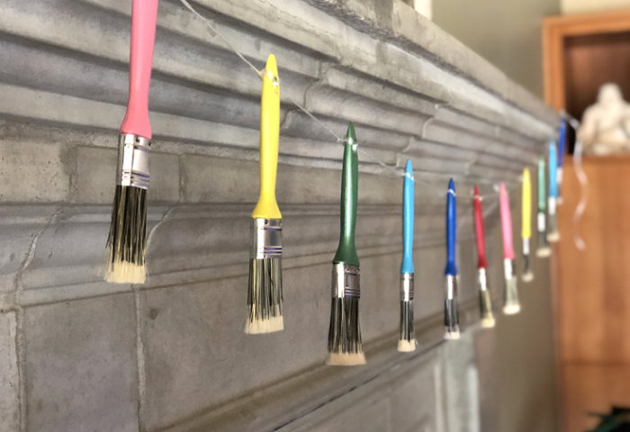 Brightly colored paint brushes hung in a garland for an Art Party