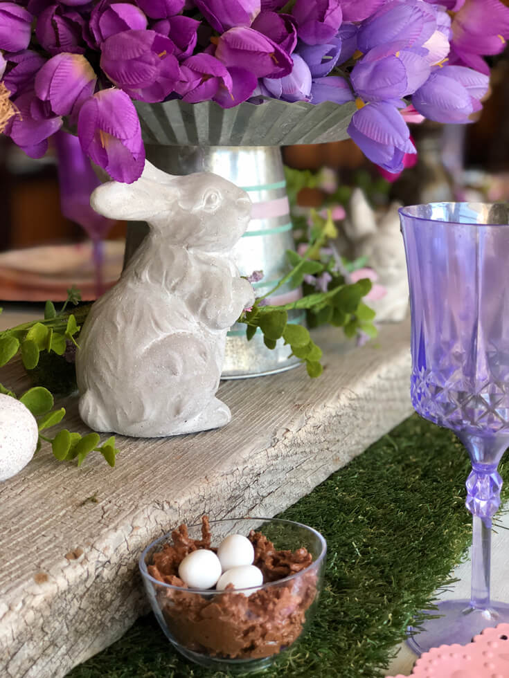 Ceramic bunny on rustic wood board with grass table runner for an Easter tablescape