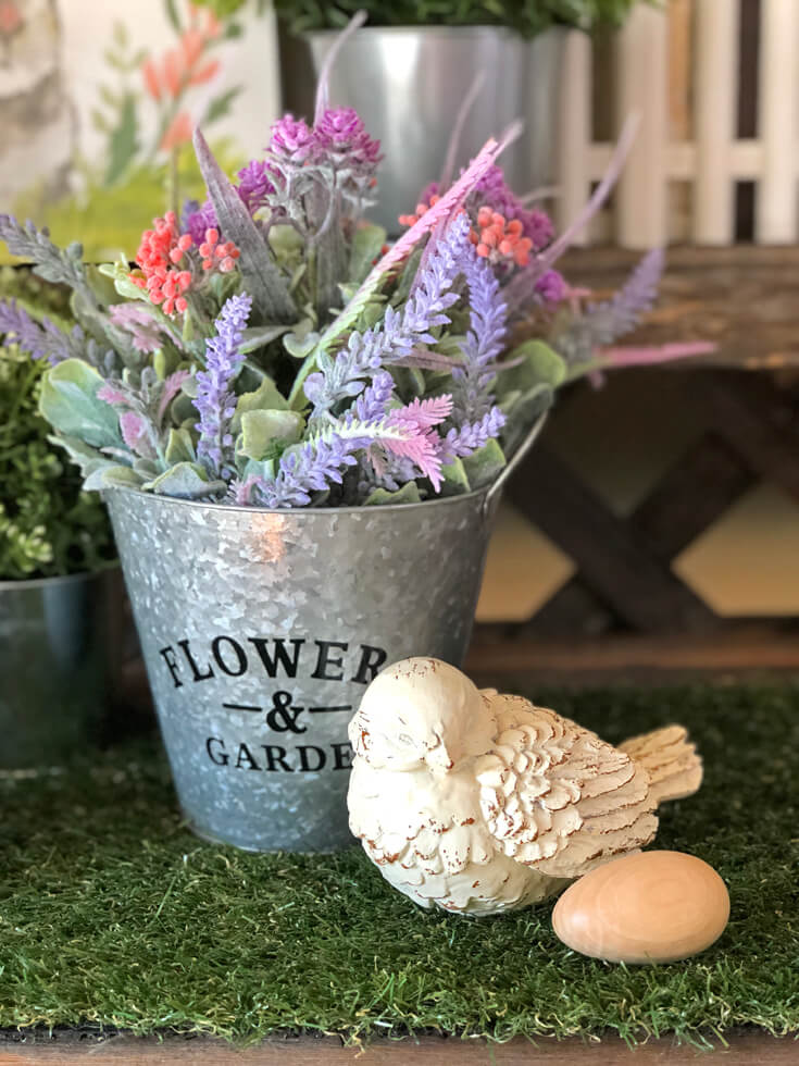 Ceramic bird and wooden egg on grass mat with galvanized bucket full of spring flowers