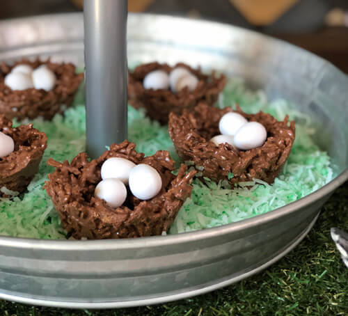 Chocolate bird nests in a bed of green coconut grass on a galvanized tray.