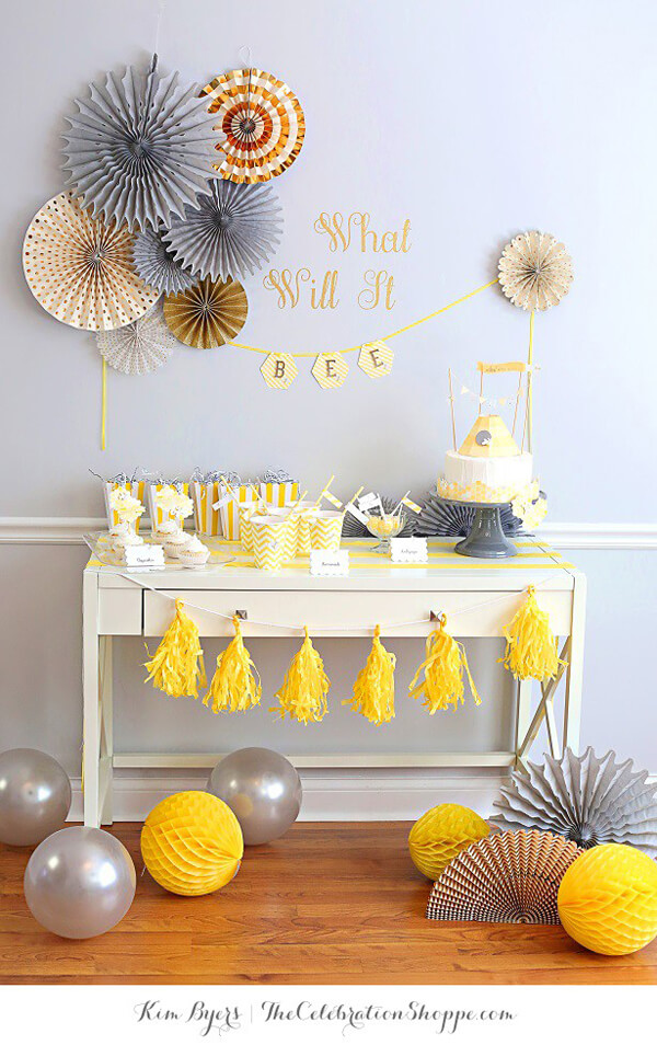 White sideboard styled with yellow and grey decor for a bee baby shower. Balloons, paper fans, tassels, and cake.