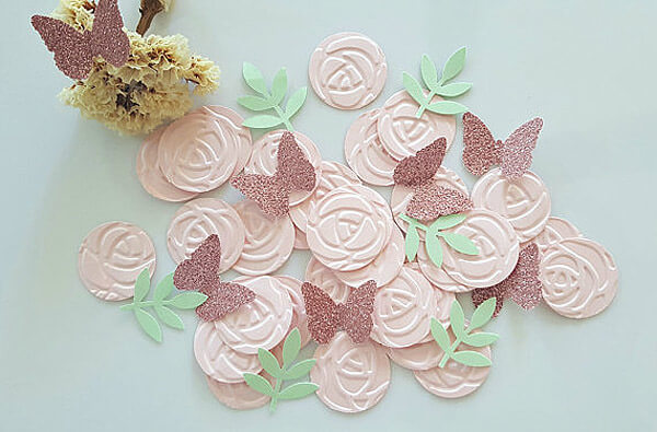 Cut roses and butterfly pieces for table scatter at an Enchanted Butterfly party.