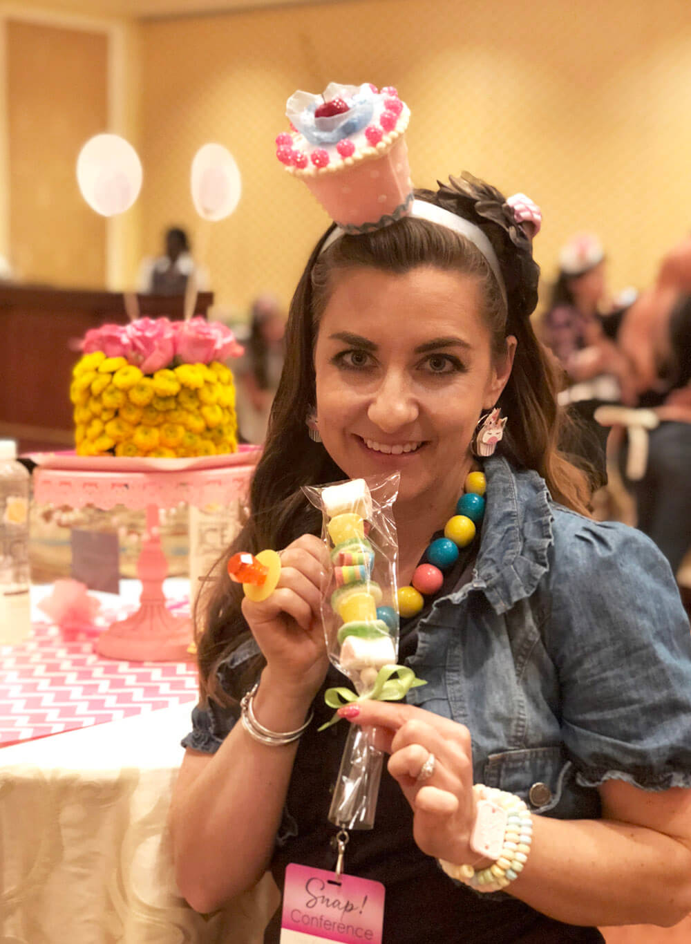 Girl holging candy kabob, wearing cupcake hat, and gumball necklace for sweets party at SNAP conference