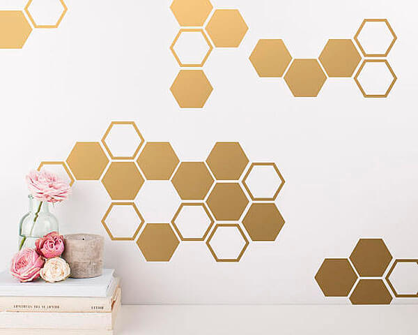 Gold vinyl hexagons as a honeycomb backdrop for a What will it bee? Gender reveal party