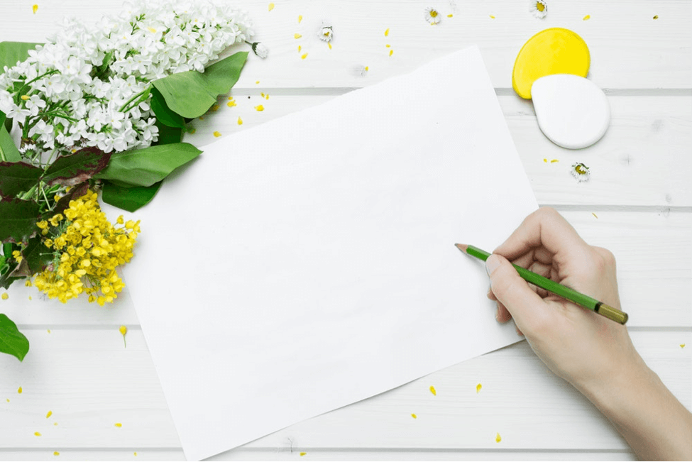 Hand about to write on blank piece of paper with floral accents on white table