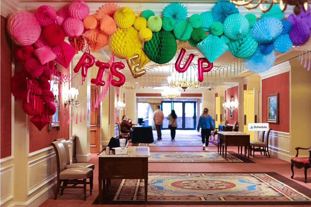 Rise Up balloon banner on rainbow colored honeycomb