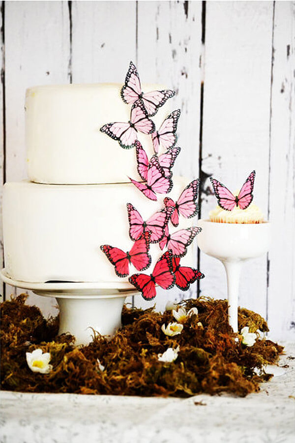 Colorful butterflies on two tiered white cake for an enchanted butterfly party.