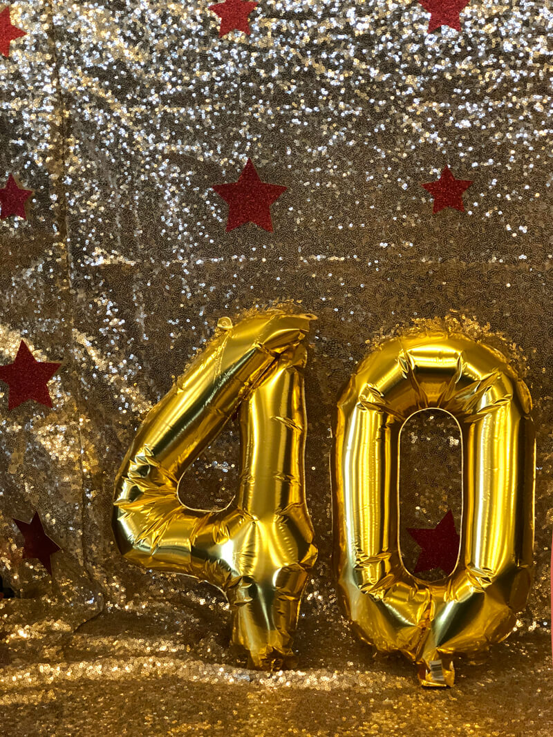 Gold sequin backdrop, number 40 balloons, red stars for Wonder Woman party
