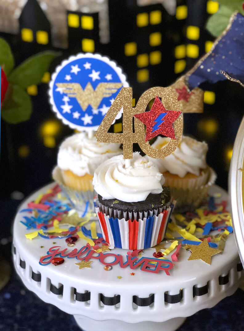 Cupcakes with Wonder Woman toppers on cake pedestal with custom confetti