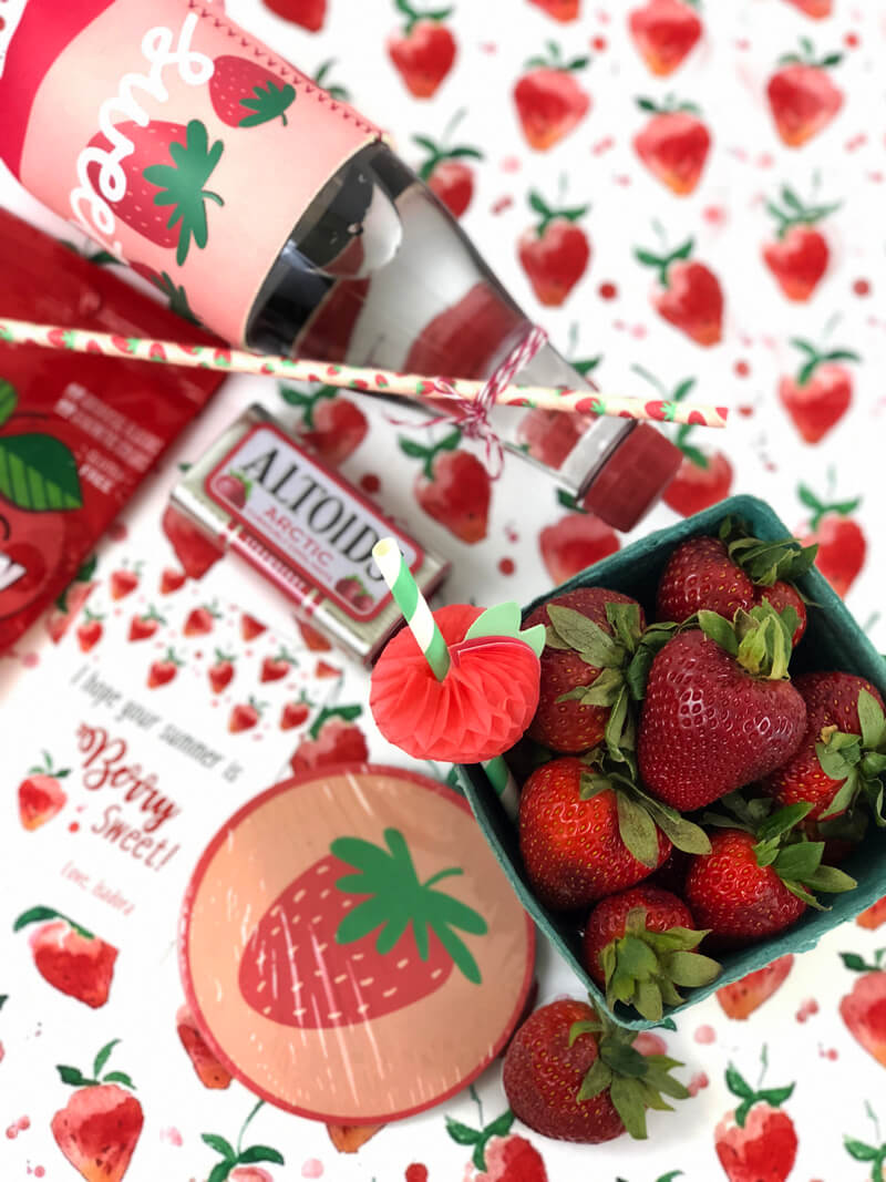 Strawberry items laid out on strawberry print paper for a Berry Sweet Summer Teacher Gift