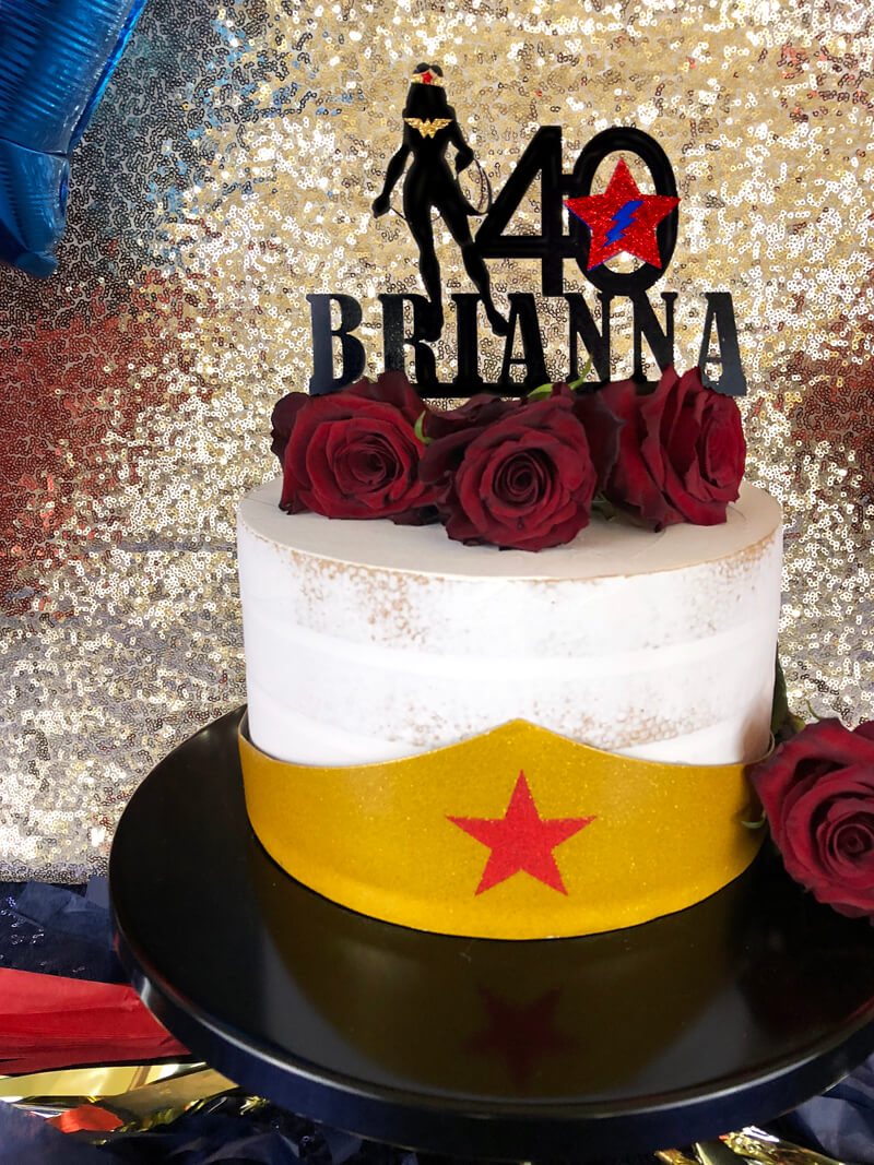 Naked cake with gold tiara topped with red roses and custom cake topper for Wonder Woman party