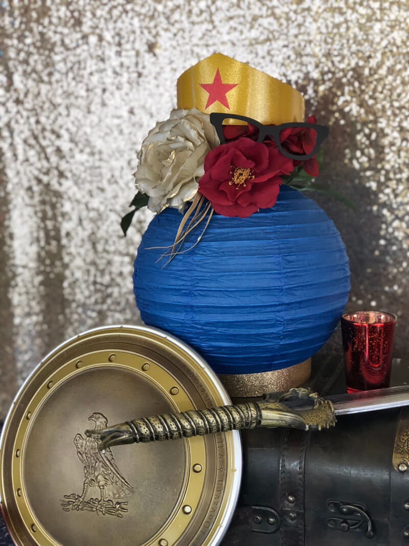 Floral lantern centerpiece with sword and shield for Wonder Woman party