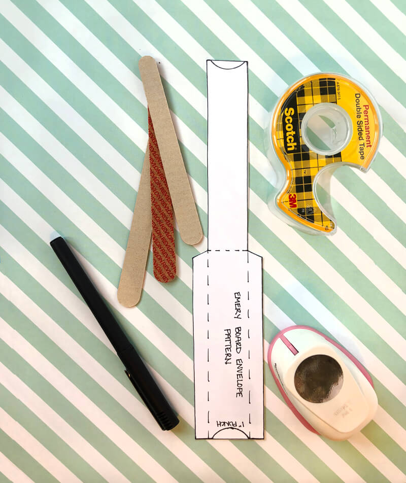 Supplies to make an emery board cover spread out on cute striped paper.
