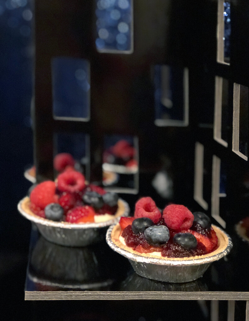 Fruit tarts on black skyscraper stand for Wonder Woman party