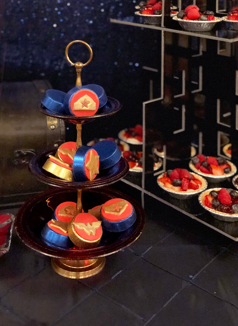 Wonder Woman themed chocolate covered Oreos on red glass tiered tray for a Wonder Woman party