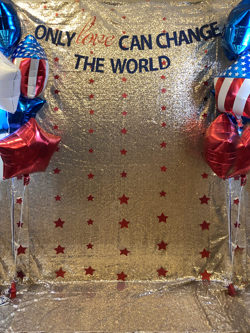 Gold sequin backdrop, red stars, and patriotic balloons for Wonder Woman party photo booth