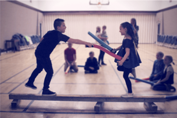 Children standing on elevated plank dueling with DIY light sabers at a Star Wars Birthday Party