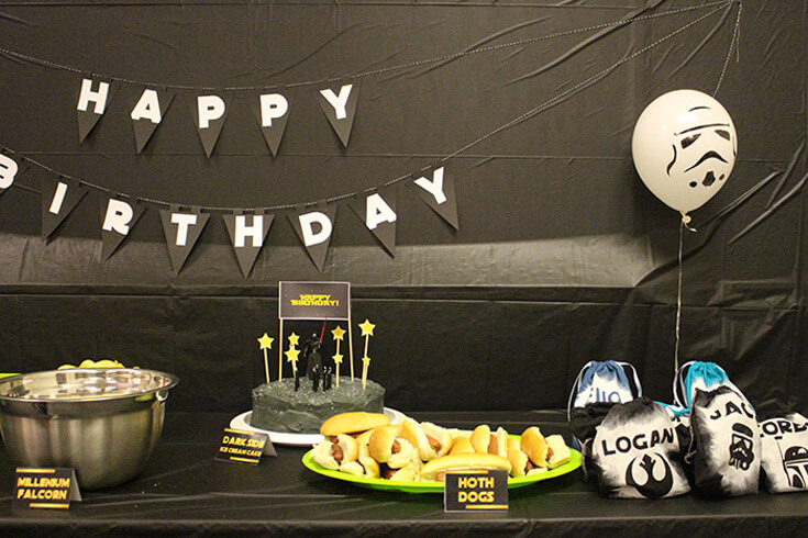 Party table with black background, happy birthday banner, and storm trooper balloons for a Star Wars Birthday Party