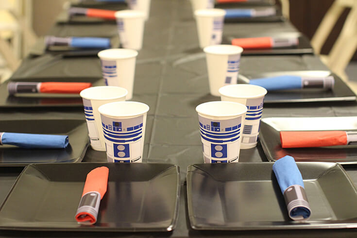Table set with black cover, plates, light sabor napkin rings, and R2D2 cups for a Star Wars Birthday Party