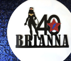 Black cake topper Wonder Woman with custom name design on white cake pedestal